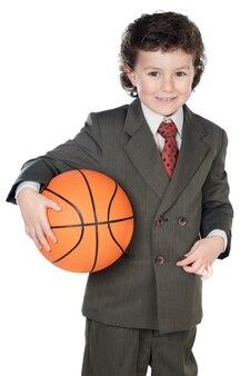 Urocza chłopiec w garniturze z piłką do koszykówki