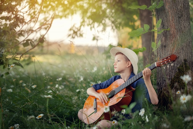 Urocza chłopiec z gitarą, relaksuje w parku. żartuje obsiadanie na trawie w letnim dniu