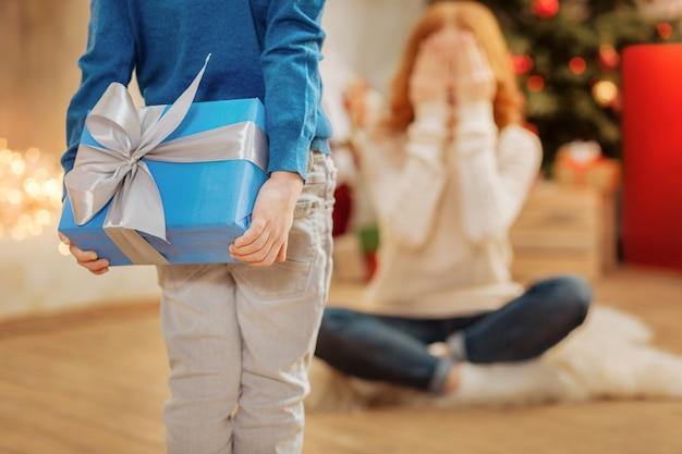 Urocza chwila. dzieciak ubrany w swobodny strój, trzymający za plecami pięknie zapakowany prezent, zaskakujący matkę w bożonarodzeniowy poranek.