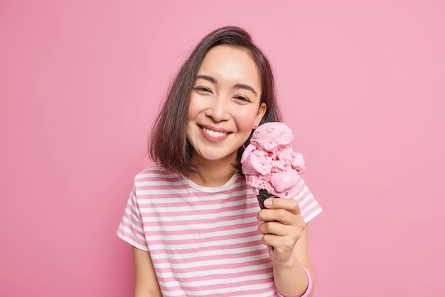 Urocza ciemnowłosa azjatka lubi jeść smaczne lody truskawkowe w upalny letni dzień ma optymistyczny nastrój zadowolony wyraz twarzy ubrany niedbale pozuje z ulubionym mrożonym deserem w pomieszczeniu