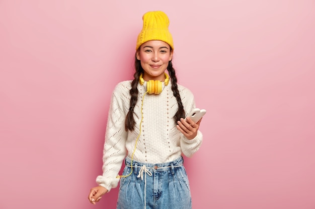 Urocza ciemnowłosa dziewczyna z warkoczykami, używa telefonu komórkowego do surfowania w sieciach społecznościowych, nosi stylowe nakrycia głowy