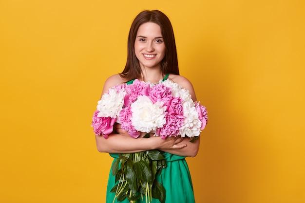 Urocza ciemnowłosa kobieta pozuje w zielonej sukni, obejmując bukiet kwiatów
