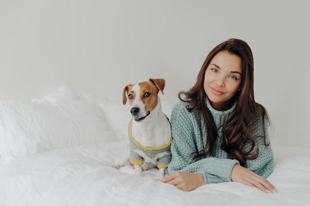 Urocza ciemnowłosa kobieta ubiera swojego psa na chłodne dni