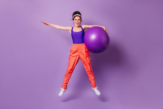 Urocza ciemnowłosa kobieta w jasnym stroju sportowym robi ćwiczenia