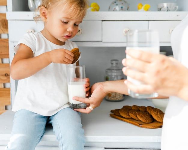Urocza córka jedzenia ciastek z mlekiem