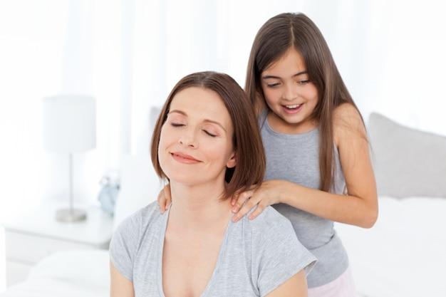 Urocza córka szczotkuje włosy kobiety