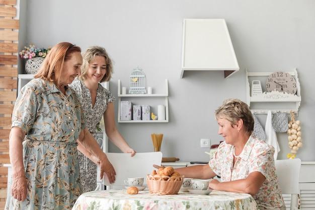 Urocza córka układa krzesło dla swojej babci w kuchni