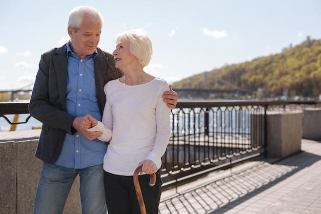 Urocza cudowna szczęśliwa para uśmiechnięta i rozmawiająca o swoim życiu idąc promenadą