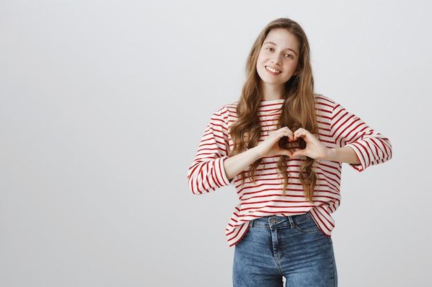 Urocza czuła dziewczyna pokazuje gest serca, pokazuje miłość i troskę