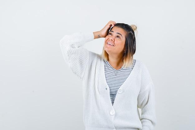 Urocza dama drapie się po głowie, patrzy w t-shirt, sweter i wesoło
