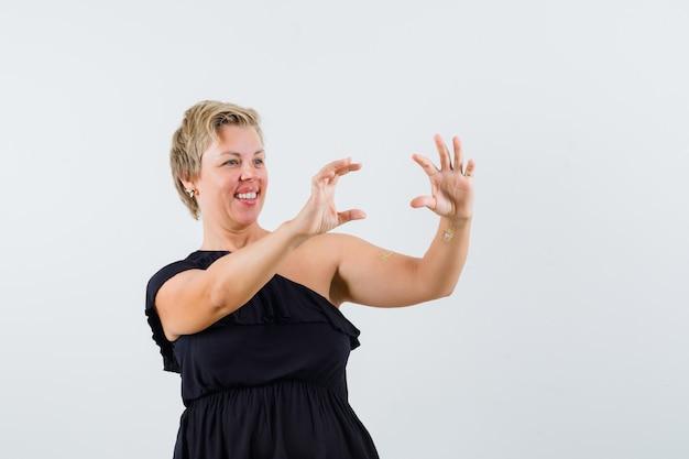 Urocza dama pozująca jak robienie zdjęcia w czarnej bluzce i wyglądająca wesoło