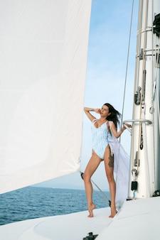 Urocza dama stoi i pozuje na żaglówce lub jachcie na morzu w nowoczesnym białym kostiumie kąpielowym