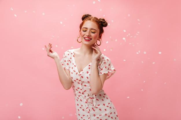 Urocza dama w białej sukni z wiśniami uśmiecha się uprzejmie. portret kobiety rude w masywnych kolczykach na różowym tle.