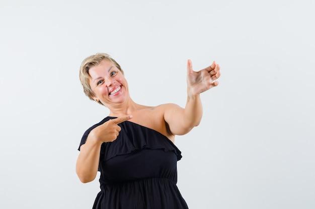 Urocza dama w czarnej bluzce udająca trzymanie telefonu, wskazując na niego i patrząc pozytywnie