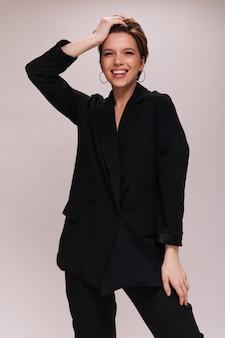 Urocza dama w czarnym klasycznym stroju uśmiechnięta na na białym tle. atrakcyjna kobieta w ciemnym garniturze, śmiejąc się i dotykając włosów