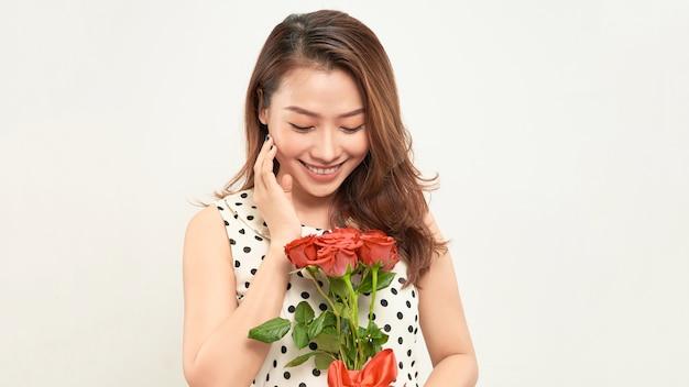 Urocza, delikatna dziewczyna trzyma w dłoniach czerwone róże i patrzy z namysłem w bok. zdjęcie na białym tle.
