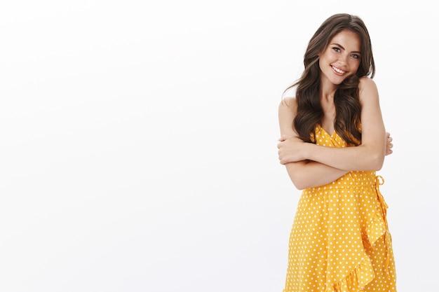 Urocza delikatna dziewczyna z głupim słodkim uśmiechem, oparta na ramieniu zalotnie śmiejąca się i szczerząca zęby, wyglądająca na rozbawioną, nosi letnią żółtą sukienkę, przytula się do rozgrzewki uczucie zimna, biała ściana