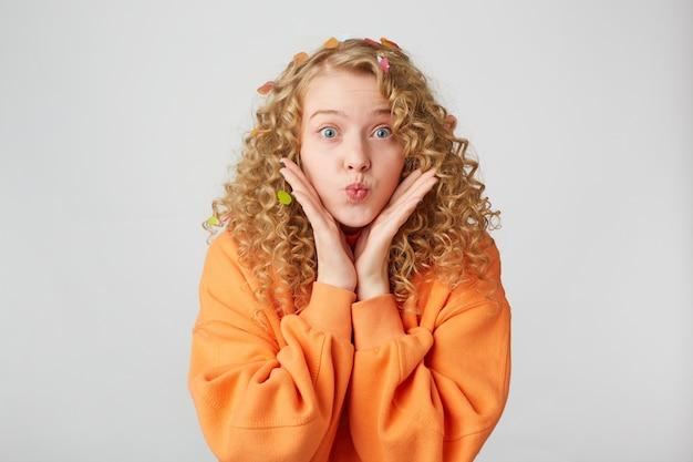 Urocza, delikatna, miła dziewczyna przesyła buziaka, trzyma dłonie blisko twarzy, jakby to demonstrowała lub próbowała zwrócić uwagę, ubrana w za dużą bluzę