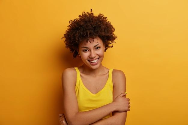 Urocza, delikatna młoda kobieta trzyma ręce skrzyżowane na ciele, uśmiecha się zmysłowo i patrzy, ma naturalne kręcone włosy, cieszy się niesamowitą chwilą w życiu, pozuje na żółtej ścianie, przyjemnie rozmawia