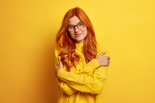 Urocza, delikatna ruda kobieta obejmuje się i czuje się komfortowo w nowym swetrze w przezroczystych okularach.