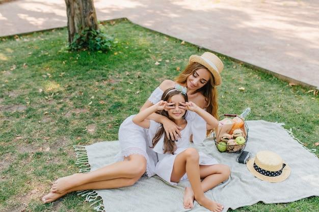Urocza długowłosa dziewczyna przyjechała do parku ze swoją młodą mamą, aby spędzić razem czas. uśmiechnięta kobieta w kapeluszu vintage, patrząc na córkę, która pozuje ze znakiem pokoju, leżąc na kocu.