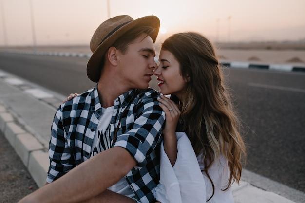 Urocza długowłosa kobieta pozuje ze swoim stylowym chłopakiem w modnej czapce, delikatnie dotykając jego ramienia. portret pięknej miłości para w ładny strój siedzi na drodze w letni wieczór