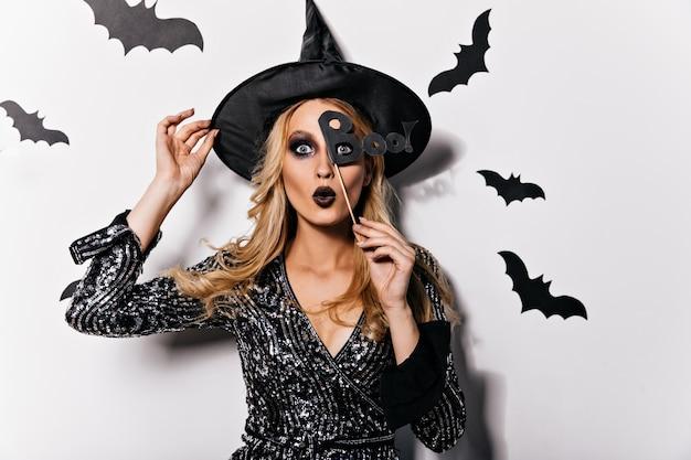 Urocza długowłosa kobieta świętuje halloween. śliczna biała dziewczyna zabawy na imprezie.