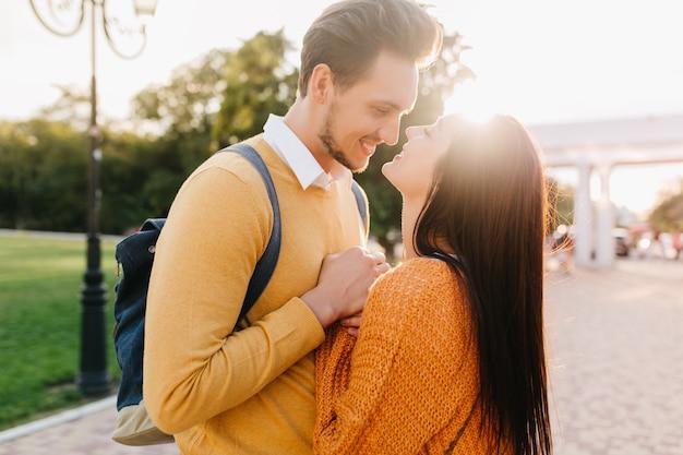 Urocza długowłosa kobieta w pomarańczowym swetrze z dzianiny, patrząc z miłością w oczy chłopaka w słoneczny jesienny dzień