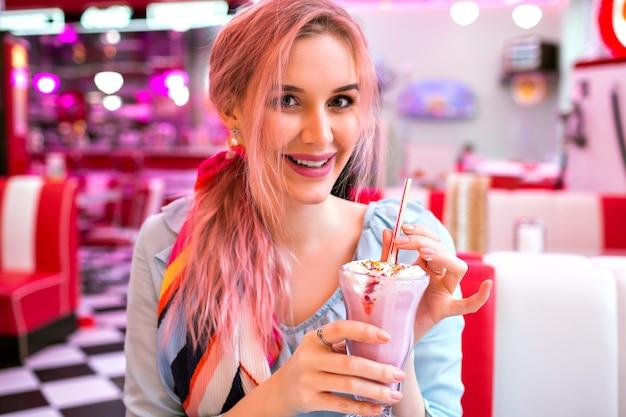 Urocza, dość zmysłowa kobieta z modnymi różowymi włosami cieszy się swoim słodkim truskawkowym koktajlem mlecznym, uśmiechniętym, modnym pastelowym strojem w stylu vintage