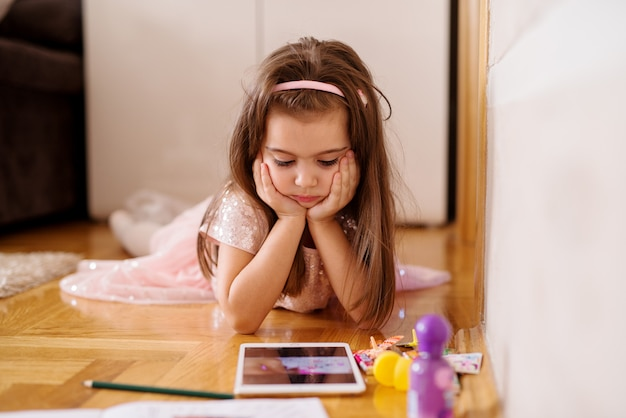 Urocza dziecko dziewczyna bawić się z pastylką na podłoga.