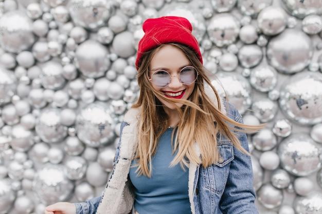 Urocza dziewczyna europejska w ładny czerwony kapelusz z radosnym uśmiechem. zdjęcie ładnej blondynki kobiety w dżinsowej kurtce stojącej obok błyszczących kulek dyskotekowych.