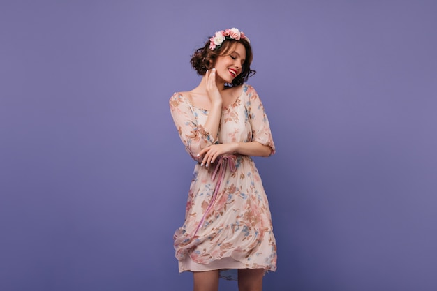 Urocza dziewczyna europejskiej w krótkiej sukience stojącej. krótkowłosa dama w wieńcu kwiatów.