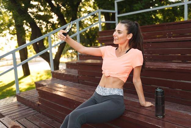 Urocza dziewczyna fitness w odzieży sportowej, uśmiechając się i robiąc zdjęcie selfie na telefon komórkowy, siedząc na ławce w parku