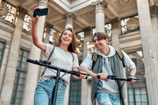 Urocza dziewczyna i atrakcyjny facet na skuterach elektrycznych robią selfie na smartfonie.