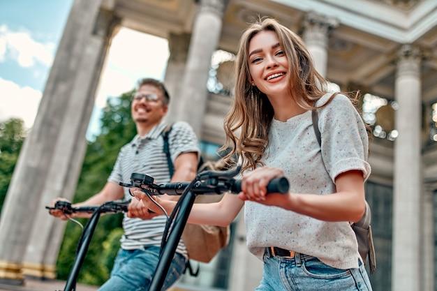 Urocza dziewczyna i atrakcyjny facet na skuterach elektrycznych.
