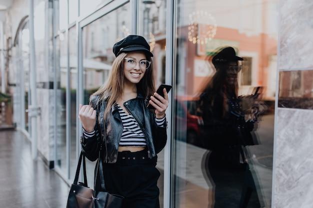 Urocza dziewczyna idzie ulicą w czarnej skórzanej kurtce po deszczu