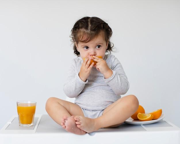 Urocza dziewczyna je pomarańcze i patrzeje daleko od
