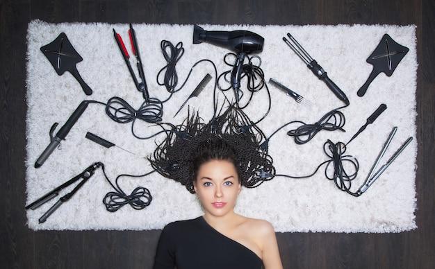 Urocza dziewczyna leży na śnieżnobiałym miękkim dywanie. dookoła znajdują się akcesoria fryzjerskie, a druty z nich rozciągają się do głowy modelki