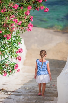 Urocza dziewczyna ma zabawę na zewnątrz. dzieciak na ulicy typowej greckiej tradycyjnej wioski z białymi ścianami i kolorowymi drzwiami na wyspie mykonos, w grecji