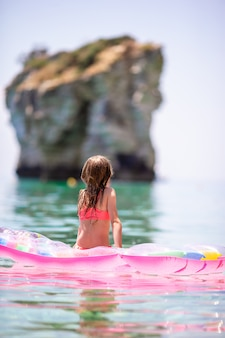 Urocza dziewczyna na dmuchanym materacu na morzu