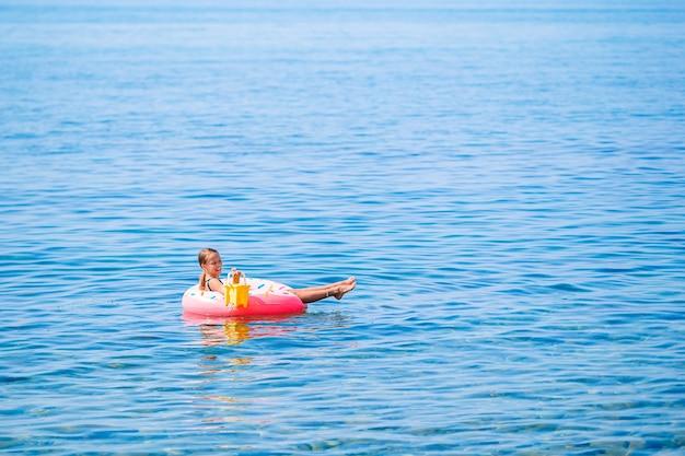Urocza dziewczyna na nadmuchiwanym materacu w morzu