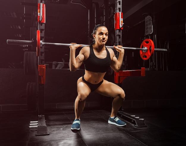 Urocza dziewczyna na siłowni kuca ze sztangą. różne środki przekazu