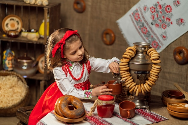 Urocza dziewczyna nalewa herbatę z samowara
