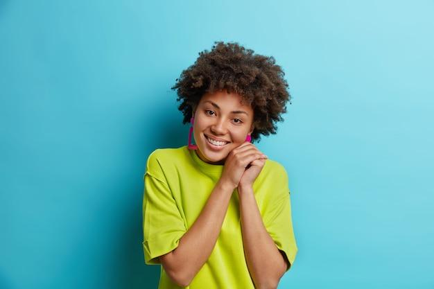 Urocza dziewczyna nastolatka ma delikatny uśmiech trzyma ręce w pobliżu twarzy