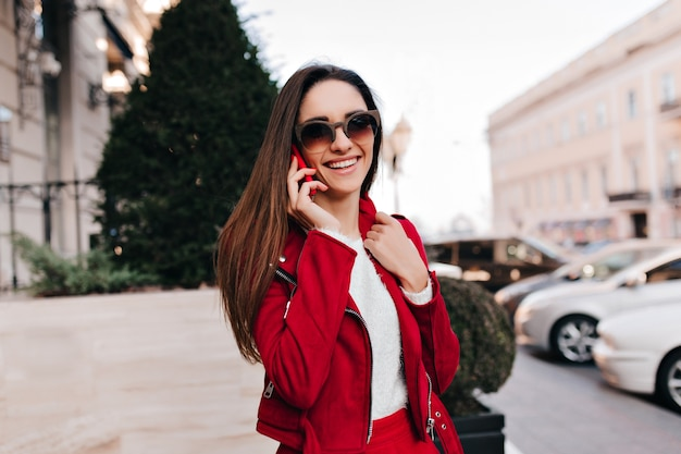 Urocza dziewczyna nosi duże brązowe okulary przeciwsłoneczne, rozmawiając przez telefon rano