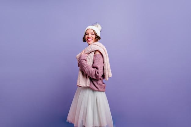 Urocza dziewczyna nosi śliczną czapkę zimową, patrząc z zaciekawieniem pozując na fioletowej ścianie. zdjęcie przystojnej wesołej pani w dzianinowych ubraniach.