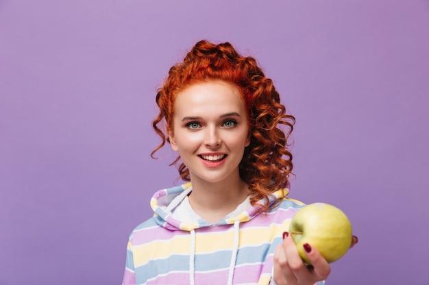 Urocza dziewczyna o niebieskich oczach uśmiecha się, patrzy z przodu i trzyma jabłko na liliowej ścianie
