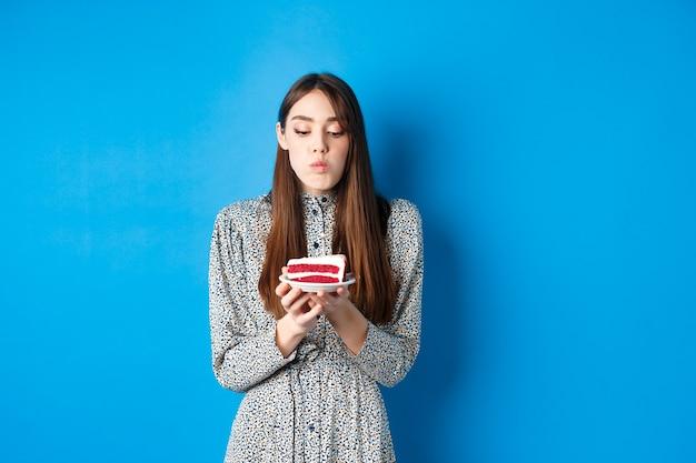 Urocza dziewczyna obchodzi urodziny, dmuchanie świeczką na torcie i życzę sobie, stojąc na niebiesko. koncepcja partii i wakacji.