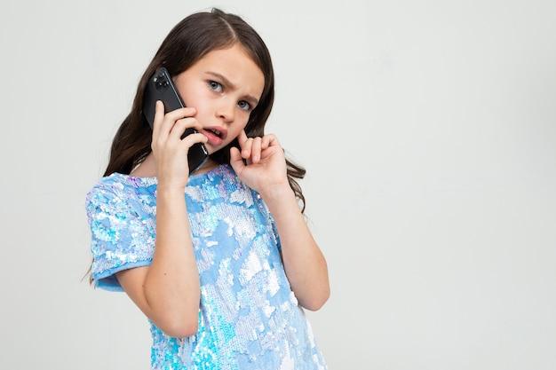 Urocza dziewczyna ostrożnie rozmawia przez telefon w rozmówcy w studio