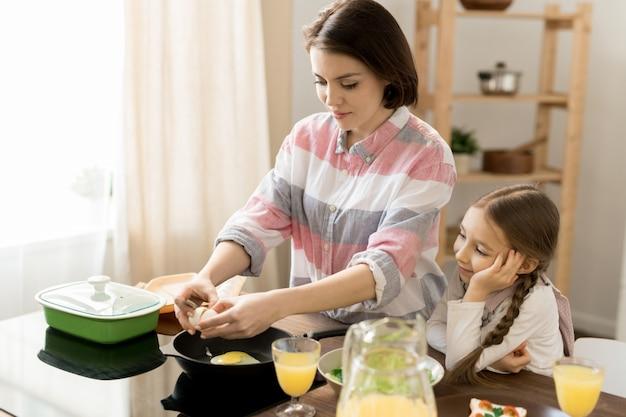 Urocza dziewczyna patrząc na mamę smażącą jajka, pomagając jej przy śniadaniu w kuchni